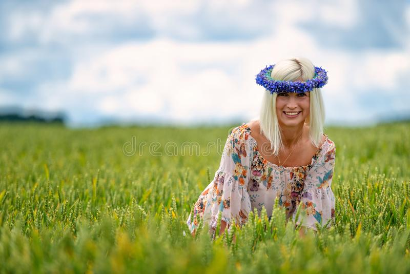 Beautiful, attractive, blonde woman with cornflower blue crown in the field of cereals.  royalty free stock photography