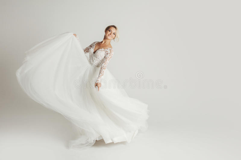 Beautiful attractive bride in wedding dress with long full skirt, white background, dance and smile royalty free stock photo