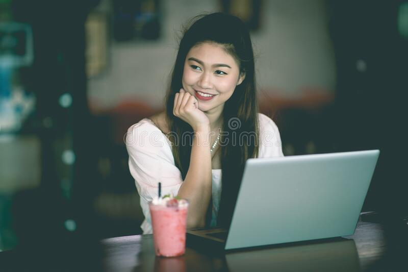Beautiful Attractive Business Asian woman working with laptop and looking in monitor smile and have positive emotional. Feeling so happiness,Business Startup royalty free stock photo