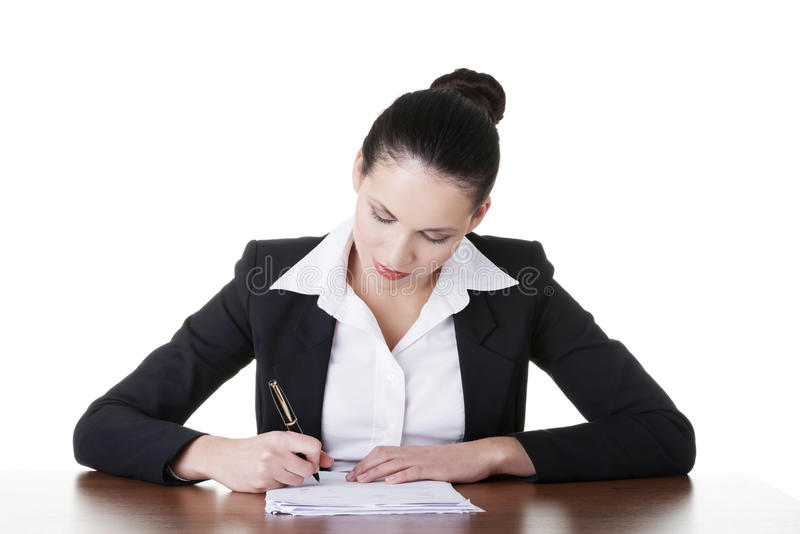 Beautiful attractive corporate lawyer business woman. Beautiful attractive corporate lawyer business woman sitting at desk and writing blank paper page royalty free stock image