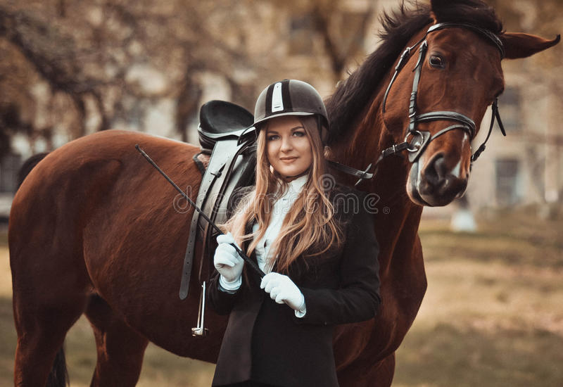 Blondie girl with a playful horse in summer horse park. stock images
