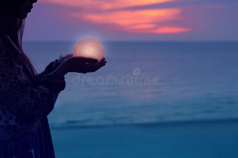 Beautiful attractive girl on a night beach with sand and stars holds the moon in her hands stock images