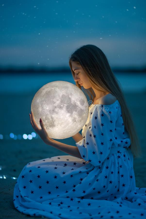 Beautiful attractive girl on a night beach with sand and stars hugs the moon, Artistic Photography stock images