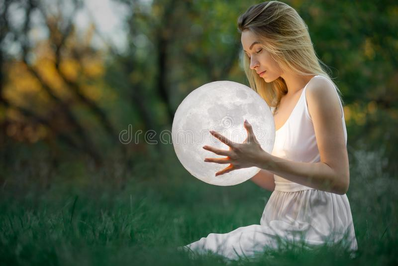 Beautiful attractive girl in a white dress in the autumn forest, hugs the moon, a mystery, a mysterious forest, artistic. Photography stock image