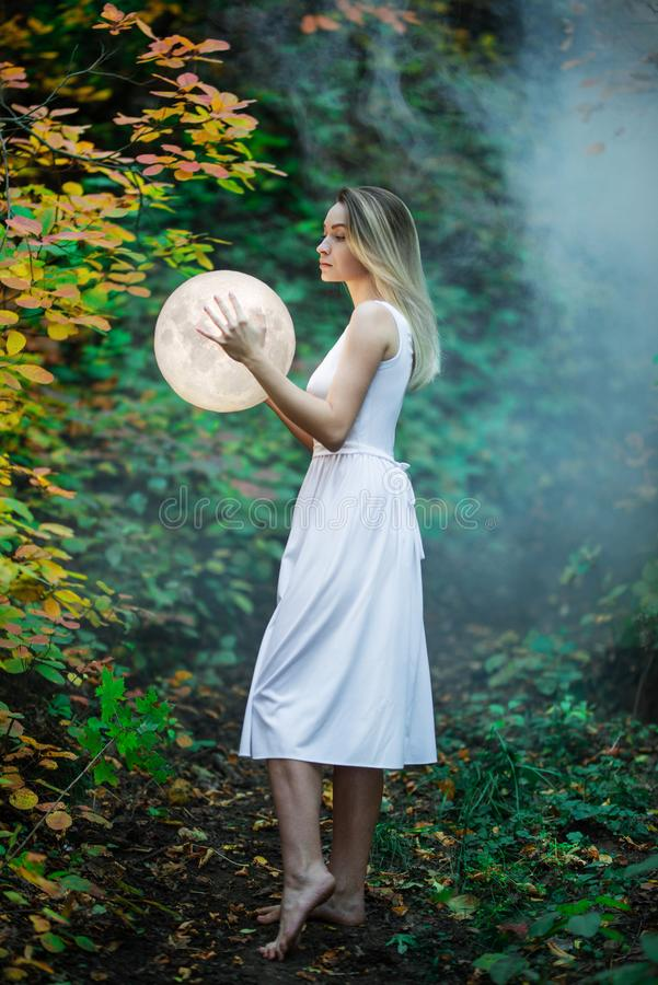 Beautiful attractive girl in a white dress in the autumn forest, hugs the moon, a mystery, a mysterious forest, artistic royalty free stock photos