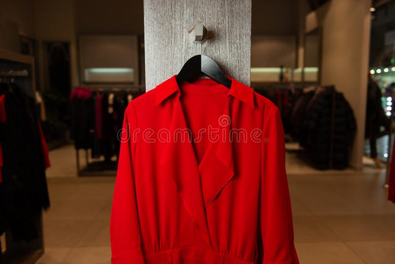 Beautiful attractive red dress with collar and cutout on hanger in retail store. New collection. Closeup view. royalty free stock photography