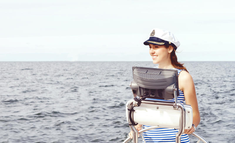 Beautiful, attractive sailor girl driving a boat. Sea, navigation concept. stock photography