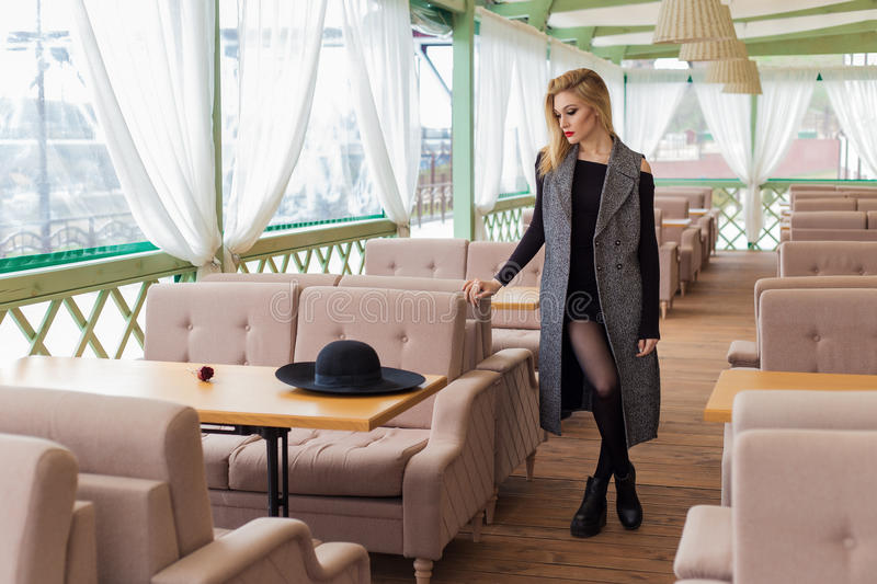 Beautiful attractive blond girl in a cafe in a black hat and coat with trendy makeup smokey eyes royalty free stock photos