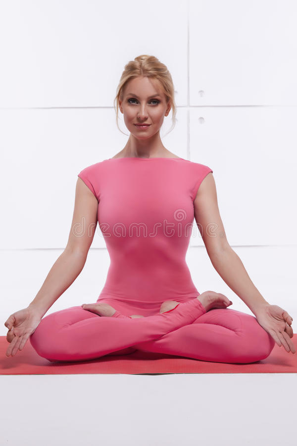 Beautiful attractive blond woman doing yoga sitting in the lotus position relaxes and opens chakras dressed in comfortabl. Beautiful attractive blond woman doing royalty free stock image