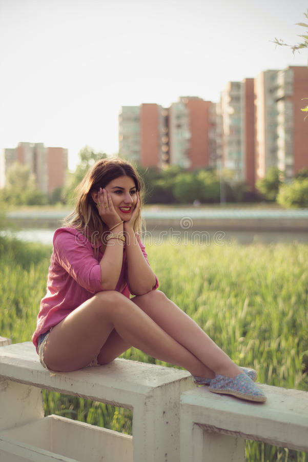 Beautiful and attractive woman sitting on a river concrete side, wearing casual denim shorts. With macrame, lace attachment, a pink shirt, floral shoes and stock photos