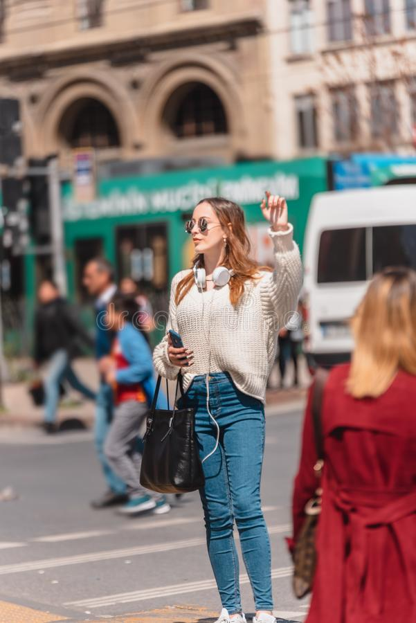 Beautiful woman looks for a taxi at street. Beautiful attractive young girl in jumper and jeans with headphones,sunglasses and smartphone looks for a taxi at royalty free stock photo