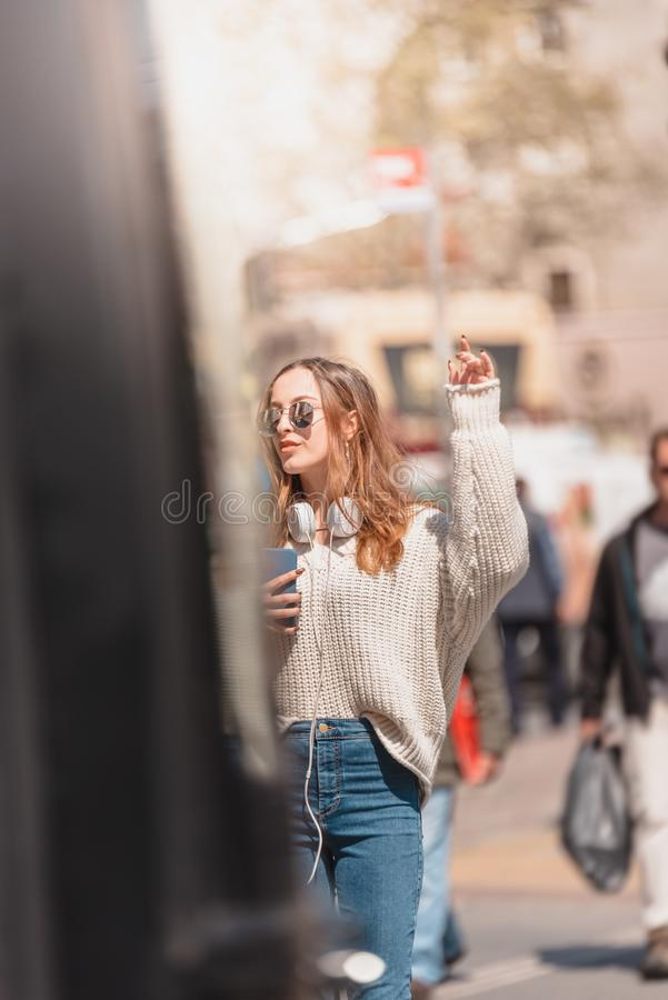 Beautiful woman looks for a taxi at street. Beautiful attractive young girl in jumper and jeans with headphones,sunglasses and smartphone looks for a taxi at stock image