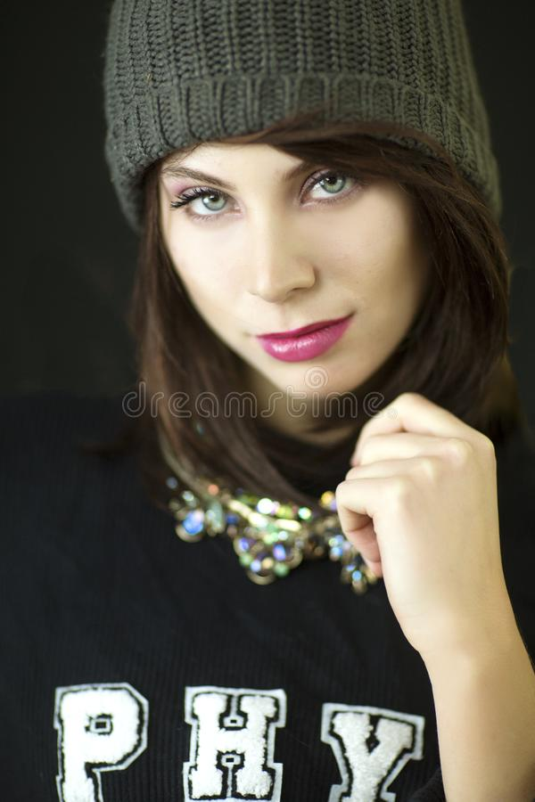 A beautiful auburn haired blue eyed woman with a knit hat and black shirt studio shot. stock images