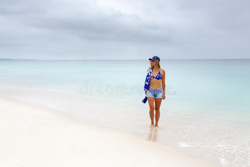 Beautiful Aussie woman walking along white sandy beach stock images