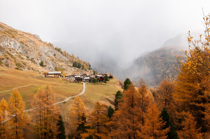 Beautiful autumn alpine landscape with many old chalets in Zermatt area royalty free stock image