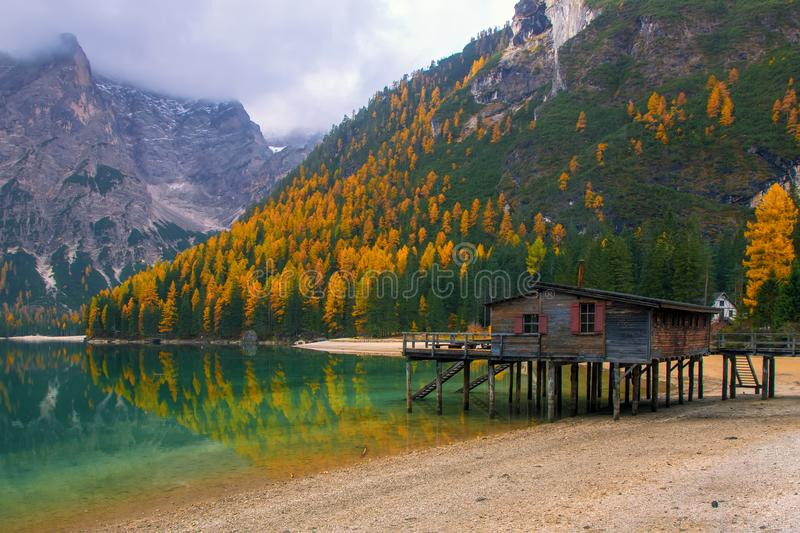 Beautiful autumn alpine landscape, spectacular old wooden dock house with pier on Braies lake, Dolomites, Italy royalty free stock photos