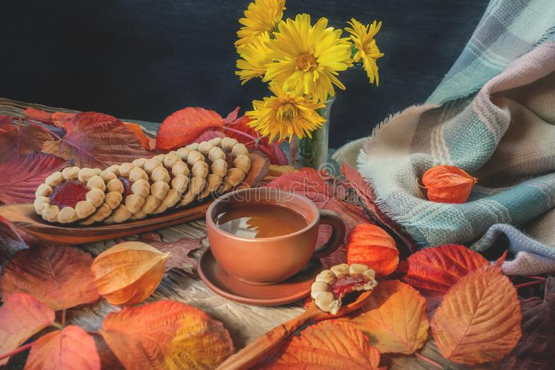 Beautiful autumn composition with tea. autumn leaves and a Cup of homemade cookies on a rustic tree background. the royalty free stock photos