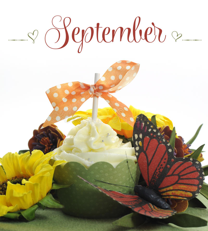 Beautiful Autumn Fall theme cupcake with autumn seasonal flowers and decorations for the month of September. With sample text or copy space for your text here stock images