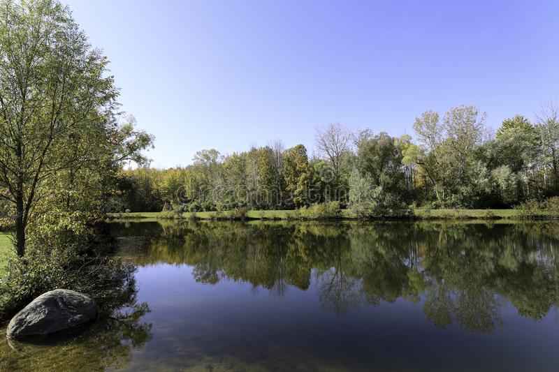 Autumn foliage reflections on the pond royalty free stock image
