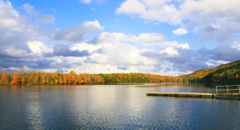 Beautiful Autumn and lake in Pocono Mountains PA. Beautiful view to the lake with pier and autumn forest beyond and blue cloudy sky in Pocono Mountains PA stock photography