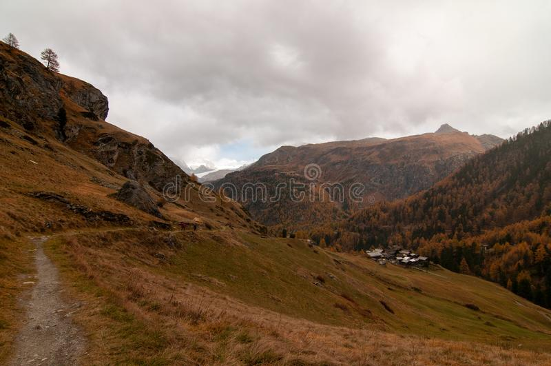 Beautiful autumn landscape with a path towards a group of chaltes in Zermatt area stock photo