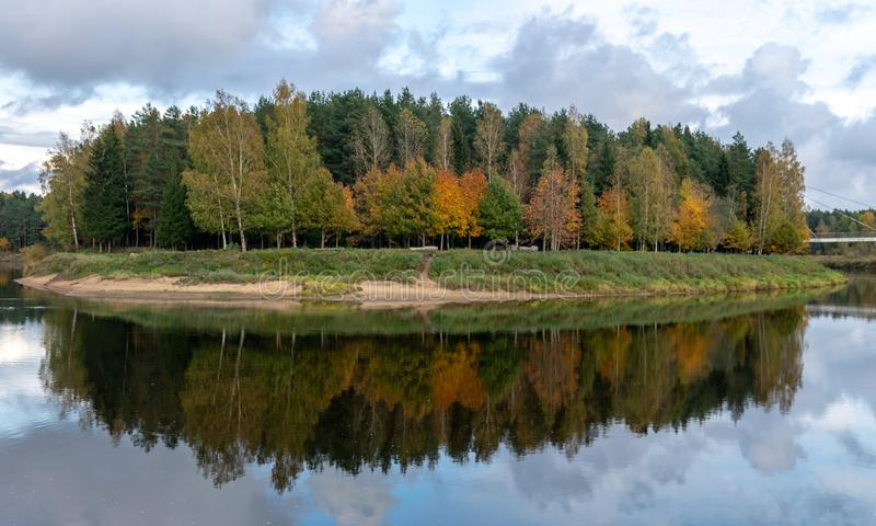 Autumn landscape with river, bridge and beautiful colorful trees, river Gauja, Valmiera, Latvia. Beautiful autumn landscape with river, bridge and beautiful royalty free stock photos