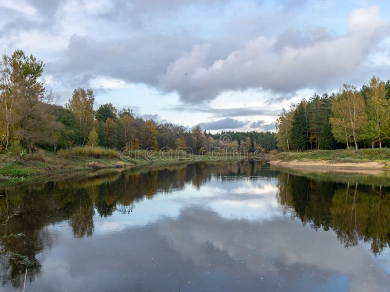 Autumn landscape with river, calm water, beautiful colorful trees, water reflections, river Gauja, Valmiera, Latvia. Beautiful autumn landscape with river, calm stock photography