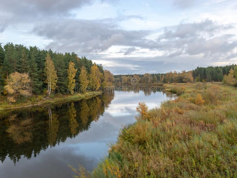 Autumn landscape with river, calm water, beautiful colorful trees, water reflections, river Gauja, Valmiera, Latvia. Beautiful autumn landscape with river, calm royalty free stock image