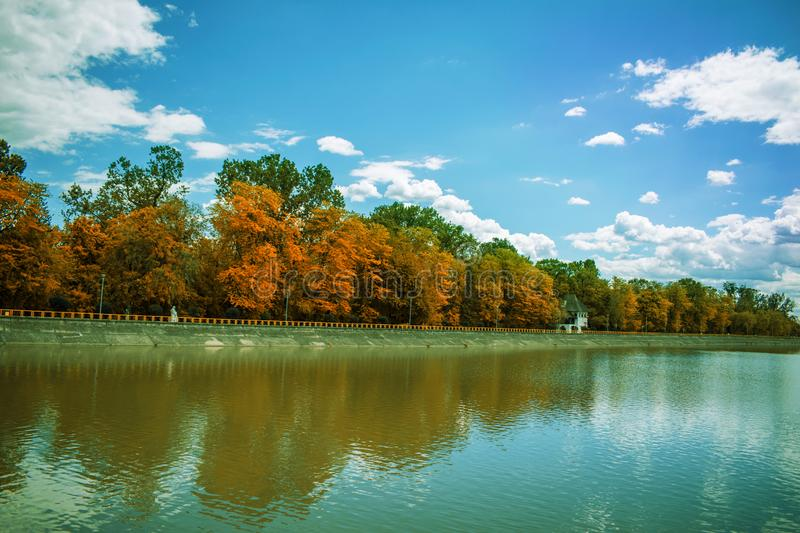 A beautiful autumn landscape. Trees with yellow leaves are reflected in the water of a lake. Autumn decoration in a beautiful park royalty free stock image