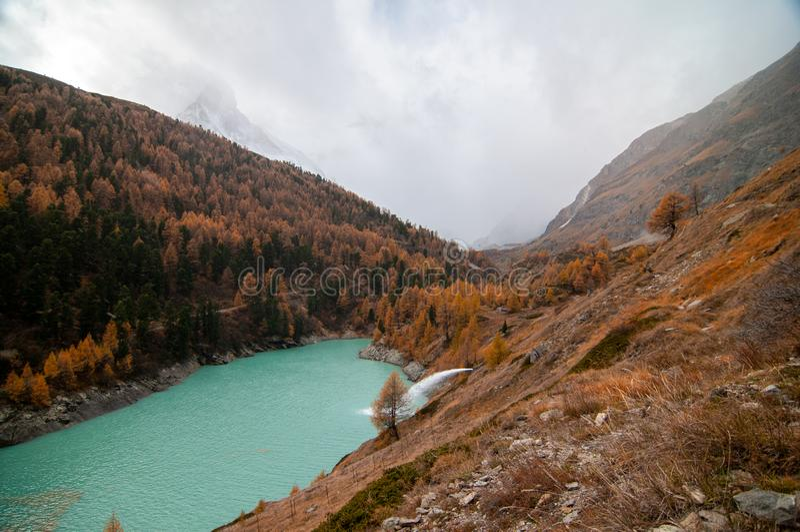 Beautiful autumn landscape with Zmuttbach Damm and Matterhorn Peak in Zermatt area stock image