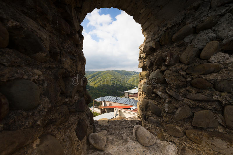 Beautiful autumn mountain landscape in Kakheti view through the. Loophole in an ancient stone wall. Georgia royalty free stock photography