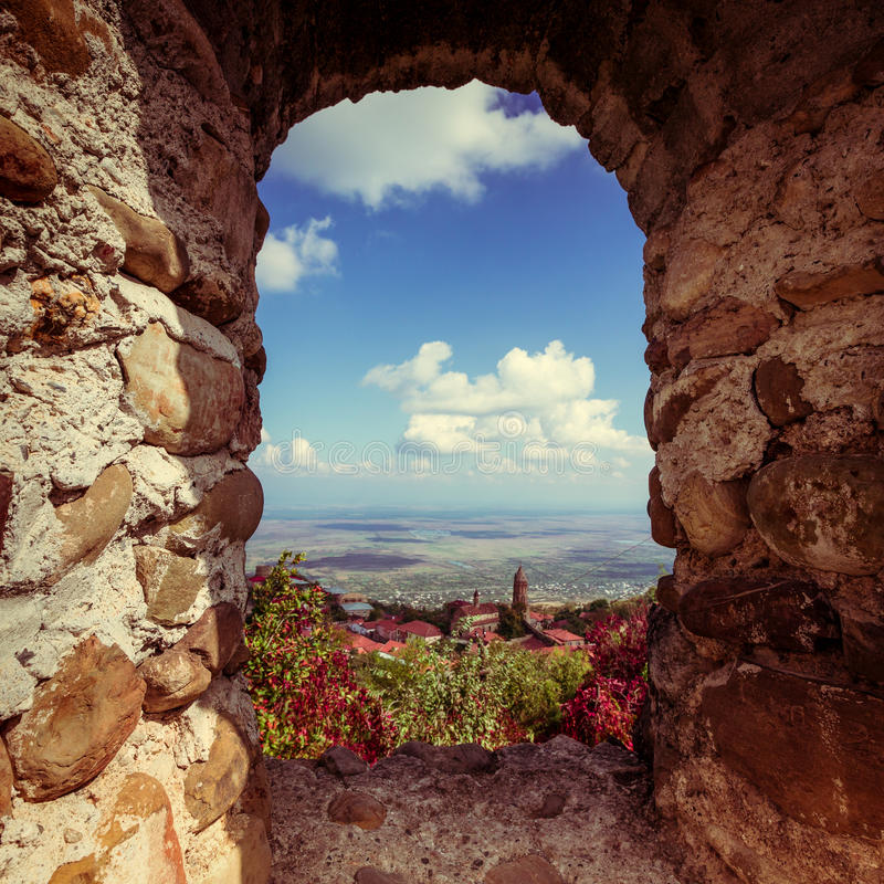 Beautiful autumn mountain landscape in Kakheti view through the. Loophole in an ancient stone wall. Georgia. Toned stock photo