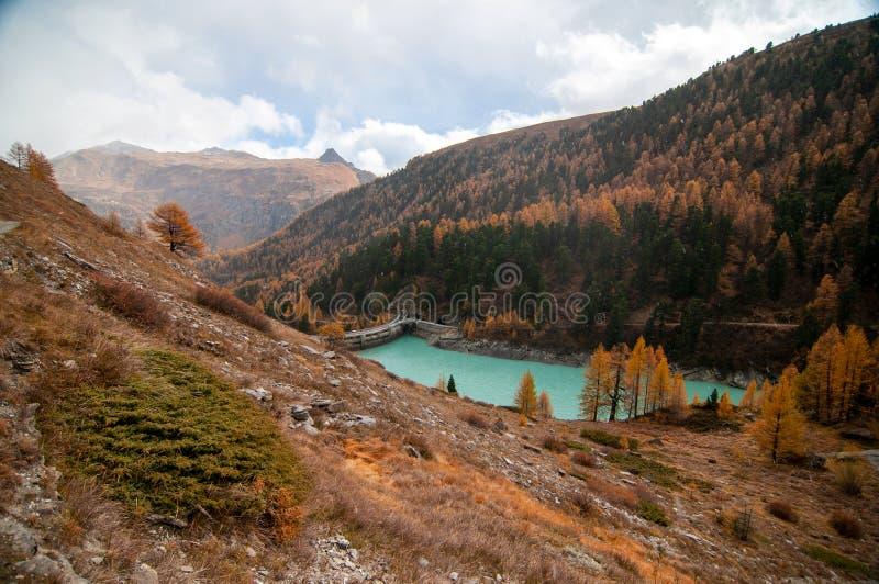 Beautiful autumn landscape with Zmuttbach Damm in Zermatt area royalty free stock image