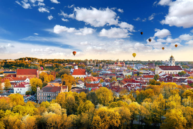 Beautiful autumn panorama of Vilnius old town with colorful hot air balloons in the sky royalty free stock photography