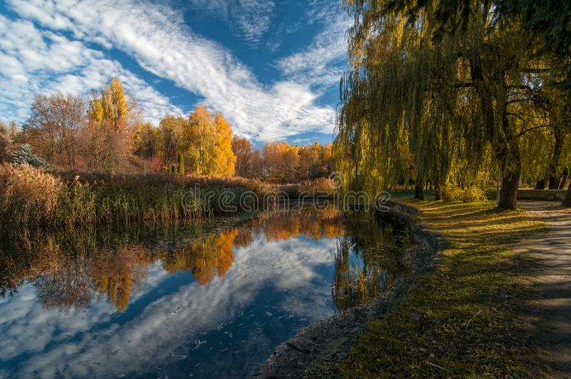 Beautiful autumn park with colorful trees and pacturesque sky reflected in the water royalty free stock images