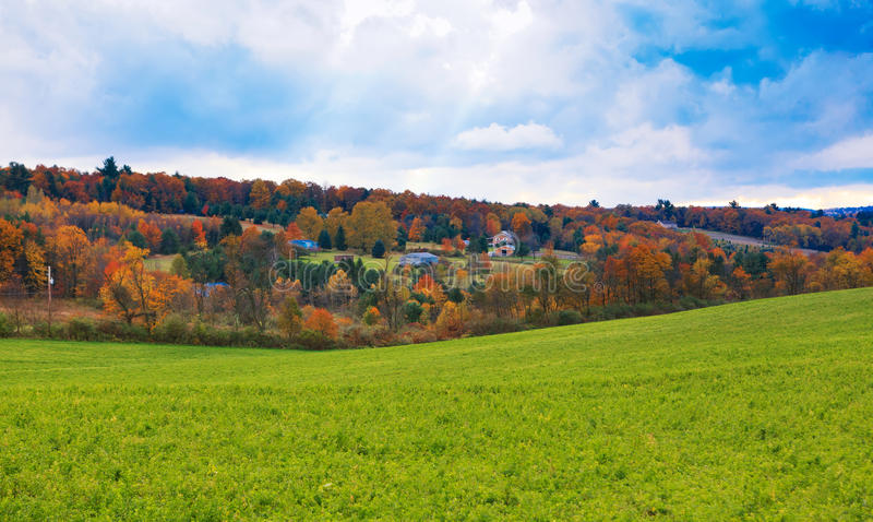 Beautiful Autumn in Pocono Mountains PA. Beautiful view of a green field and hills with autumn trees and few houses in Pocono Mountains PA royalty free stock photo