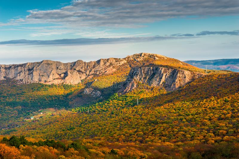 Beautiful autumn scenic landscape - orange forest and rocky mountains in the sun royalty free stock photography
