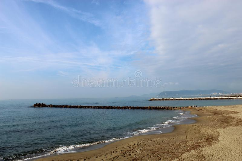 A beautiful autumn sunny day at the beach. This is the beach in Marina di Massa in Italy. It was a sunny day. The sea was calm. Beautiful blu color royalty free stock photography