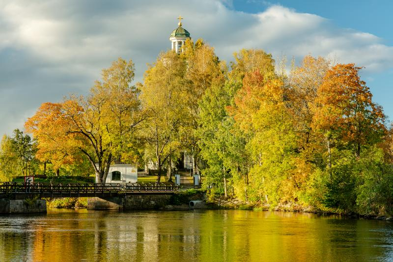Beautiful autumn view across a river with colorful trees in bright sunlight royalty free stock image