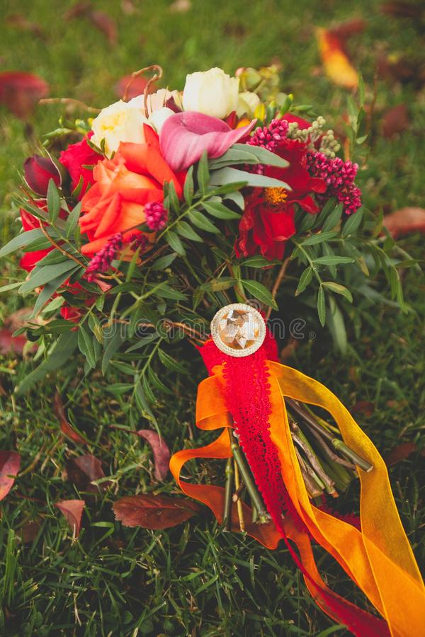 Beautiful autumn wedding bouquet of the bride is on the grass. Beautifully decorated with satin ribbons and jewelry bouquet royalty free stock photo