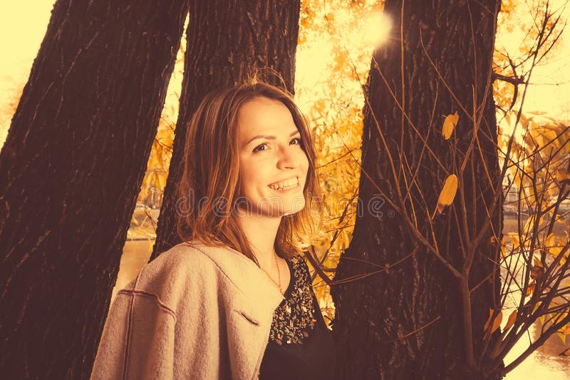 Beautiful autumn woman in city park in autumn. Outdoor lifestyle portrait of young beautiful lady. Brown hair and eyes. Warm stock images