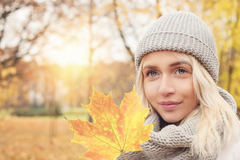 Beautiful autumn woman holding yellow maple leaf royalty free stock images