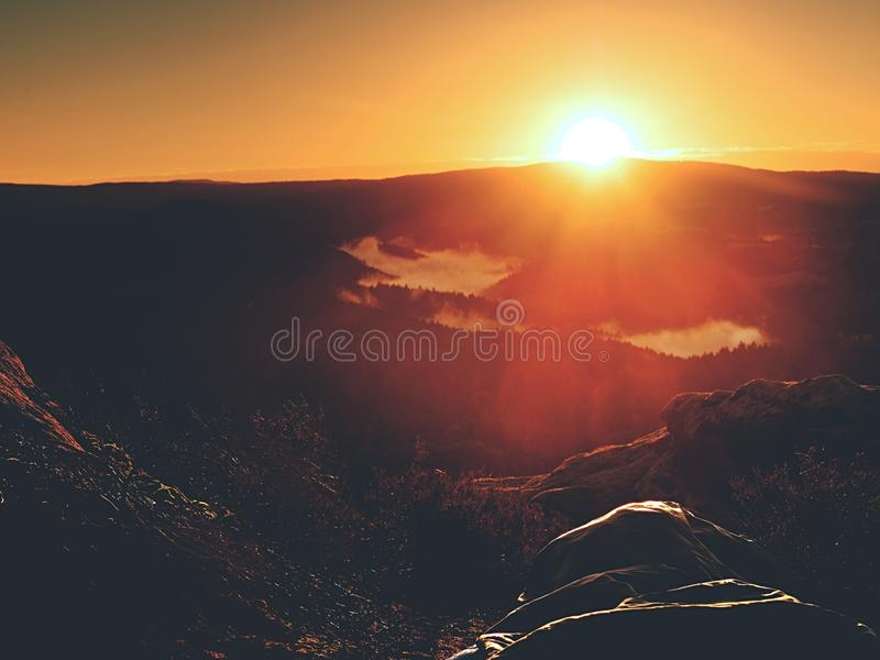 Beautiful awakening in rocks. Sleeping in nature in sleeping bag. View from rocky peak. Over forest valley stock photo