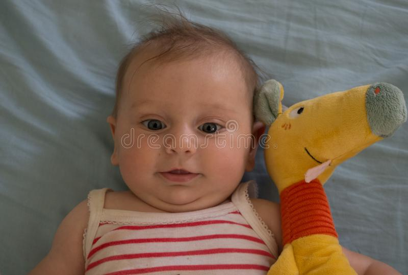 Beautiful baby with blue eyes smile with puppet. Beautiful baby with blue eyes play nice expression smile infant with speak play cross eyed puppet royalty free stock photography