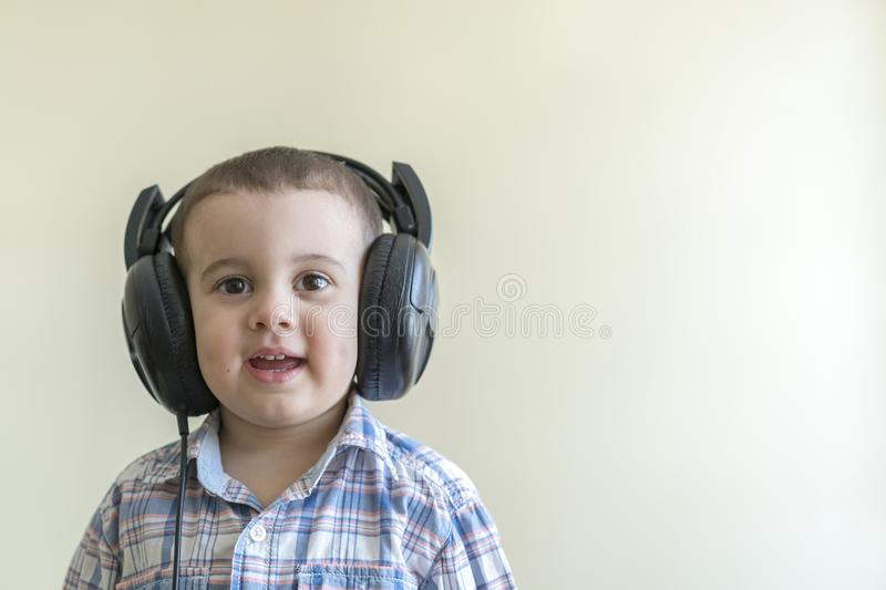 Beautiful baby boy in big headphones. A boy in a plaid shirt listening to music. copy space stock photos