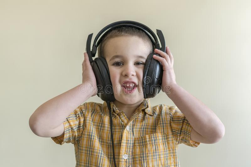 Beautiful baby boy in big headphones. A boy in a plaid shirt listening to music. toddler boy in black headphones. the kid in the h royalty free stock image