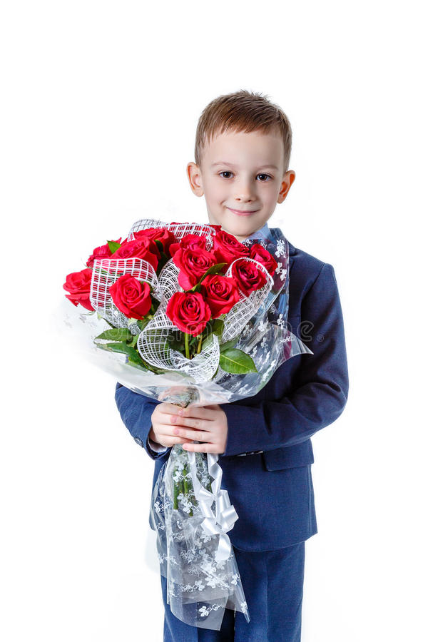 Beautiful baby boy in a suit with a bouquet of red roses on a white background royalty free stock images