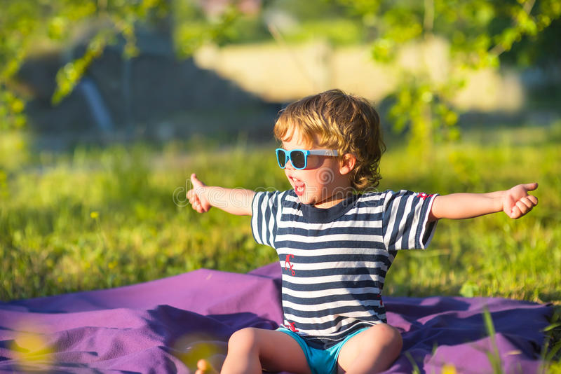 Beautiful baby child in sunglasses gesture class. Outside stock image