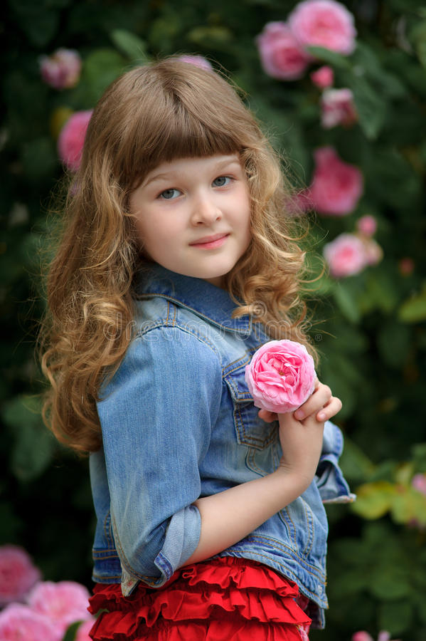 Beautiful baby child walking in the garden near the bushes with. The Beautiful baby child walking in the garden near the bushes with pink roses royalty free stock photo