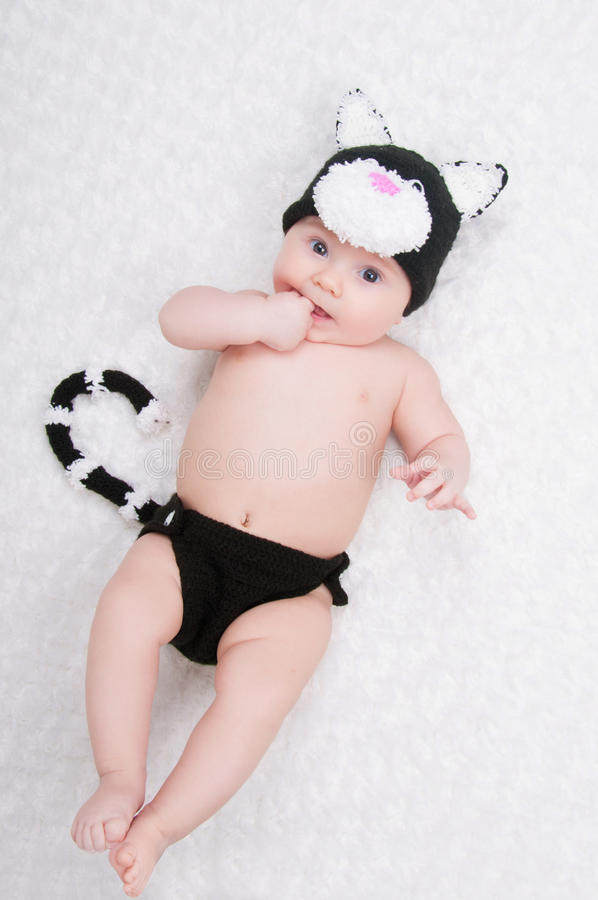 Beautiful baby in funny costume with cat ears and a tail. royalty free stock photos